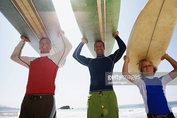 Low angle view of three generations carrying surfboards