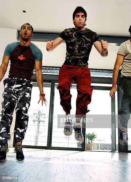 Low angle view of three men jumping