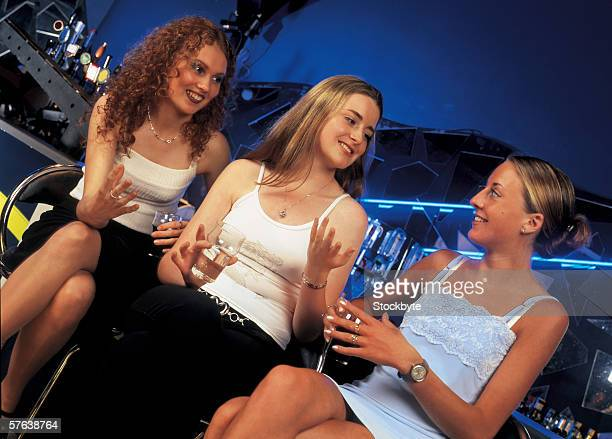 low angle view of three young women having drinks at a bar