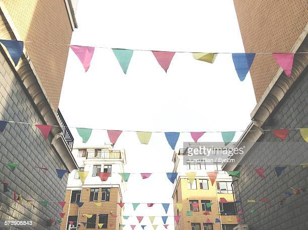 Low Angle View Of Triangle Shape Multi Colored Flags Decorated Amidst Buildings In City