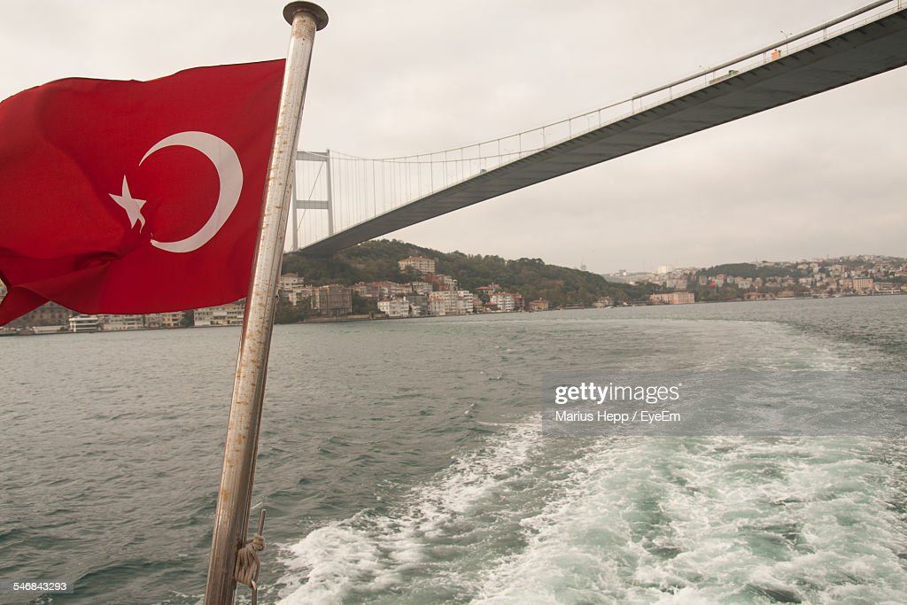 Low Angle View Of Turkish Flag Against Bosphorus Bridge Over River