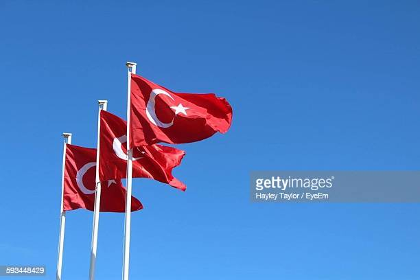 Low Angle View Of Turkish Flags Against Clear Blue Sky