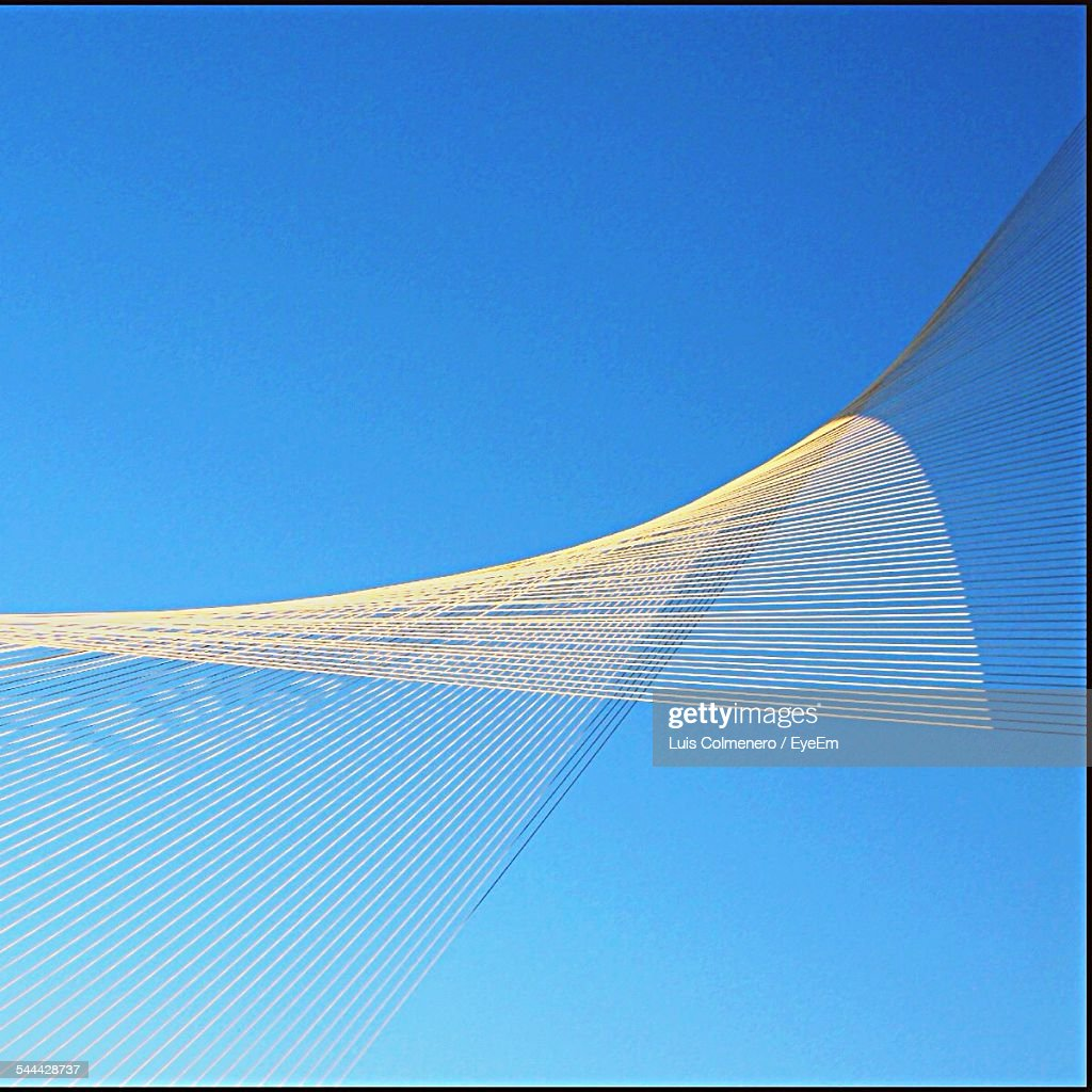 Low Angle View Of Twisted Ropes Against Clear Blue Sky