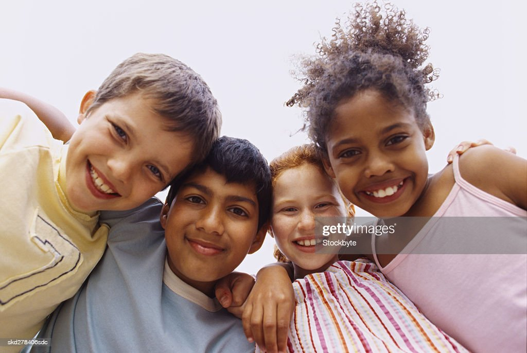 Low angle view of two boys and two girls (6-8) standing in a huddle : Stock Photo