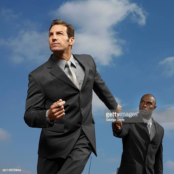 low angle view of two businessmen exchanging baton in a relay race