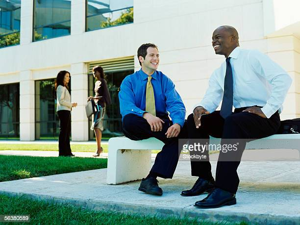 low angle view of two businessmen sitting on a bench
