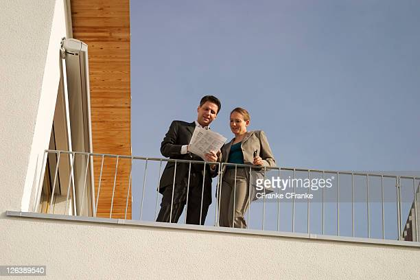 Low angle view of two businesspeople looking at documents on terrace