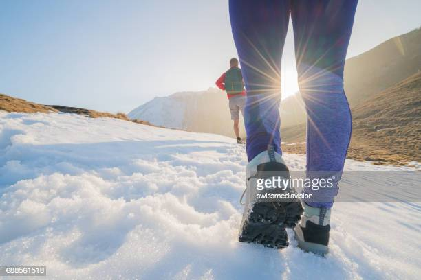 Low angle view of two hikers on snowy mountain trail