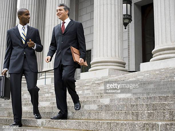 Low angle view of two male lawyers talking on the steps of a courthouse