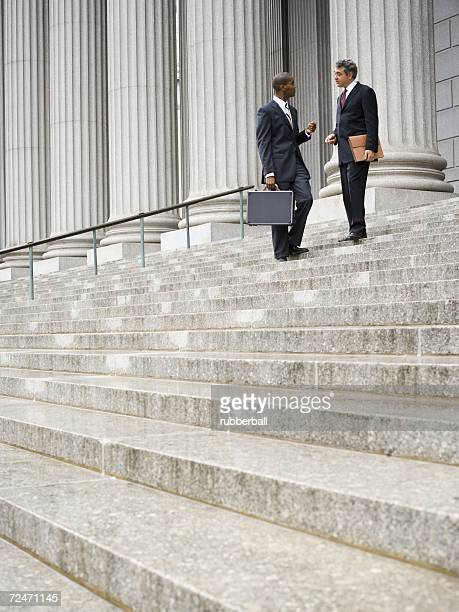 Low angle view of two men standing on the steps of a courthouse