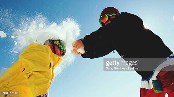 Low angle view of two people having snow ball fight against blue sky