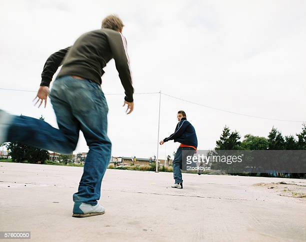 Low angle view of two young men chasing each other