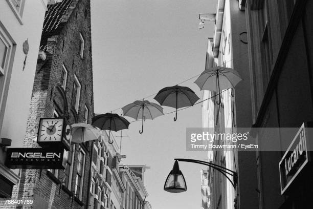 Low Angle View Of Umbrellas Hanging In City Against Clear Sky