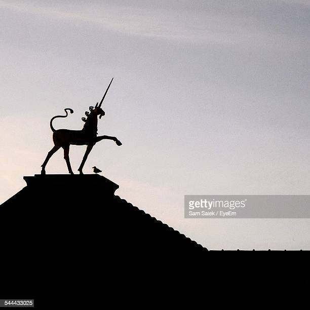 Low Angle View Of Unicorn Statue And Bird On Roof Against Sky