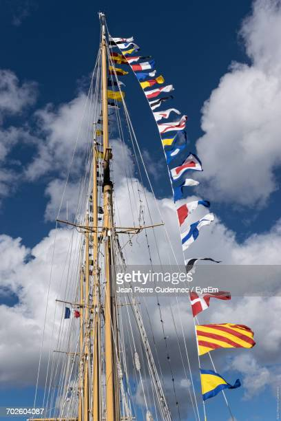 Low Angle View Of Various Flags On Mast Against Cloudy Sky