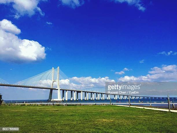 Low Angle View Of Vasco Da Gama Bridge By Grassy Field Against Cloudy Sky