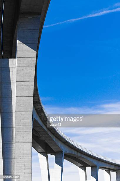 Low angle view of viaduct against bright blue sky