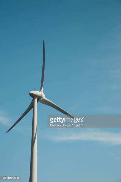 Low Angle View Of Windmill Against Blue Sky