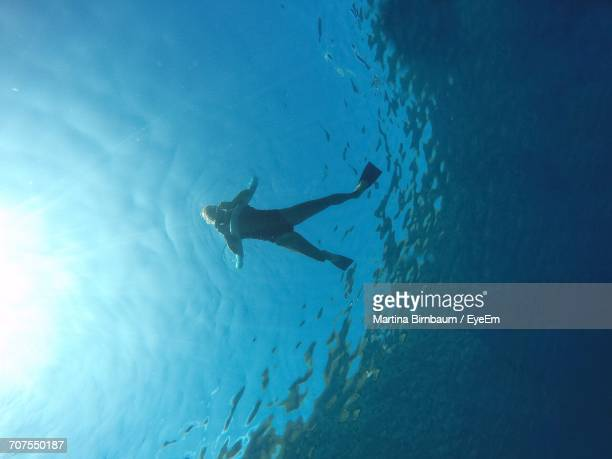 Low Angle View Of Woman Floating On Sea During Sunny Day