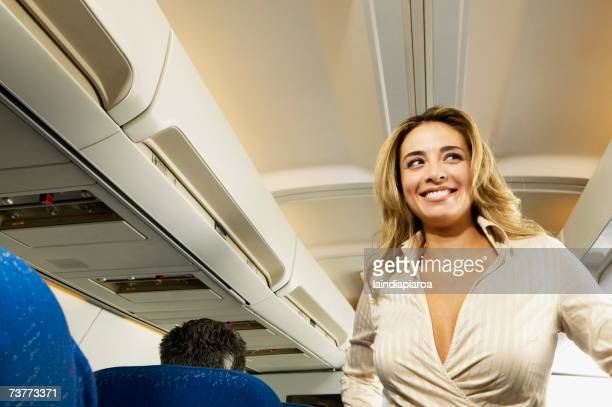 Low angle view of woman in aisle of airplane