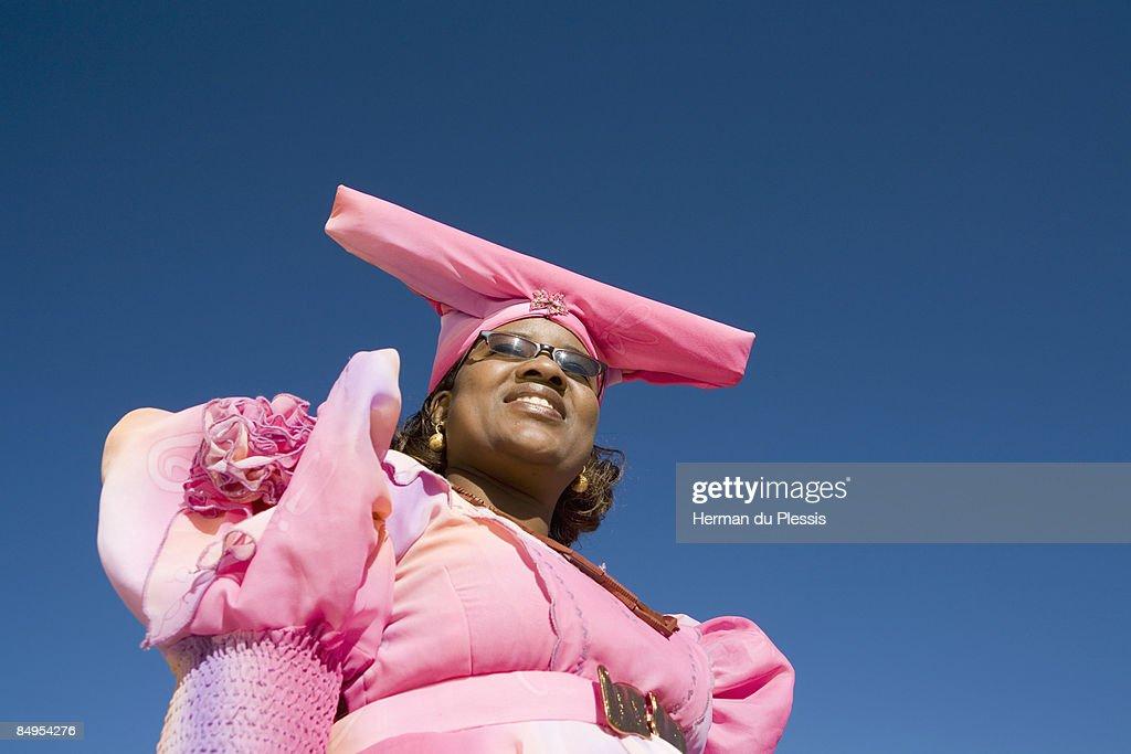Low angle view of woman in traditional Herero dress, Opuwo, Kaokoland, Namibia : Stock Photo