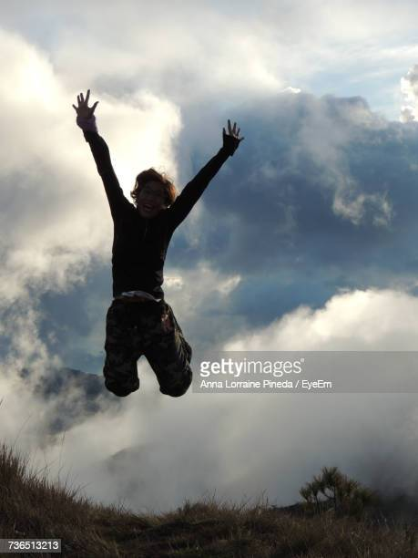 Low Angle View Of Woman Jumping On Hill Against Cloudy Sky