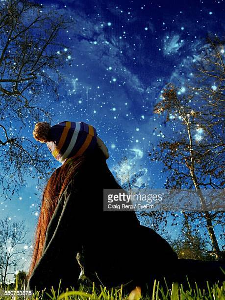 Low Angle View Of Woman Looking At Star Field In Sky At Dusk