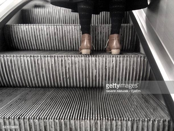 Low Angle View Of Woman On Escalator