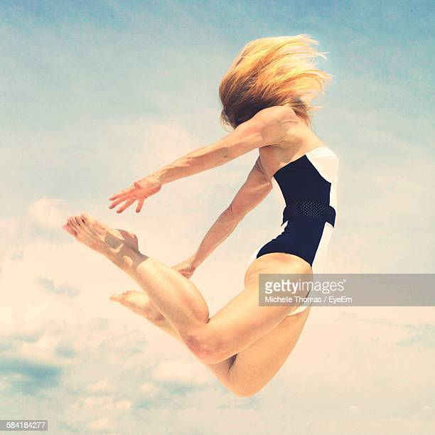 Low Angle View Of Woman Performing Yoga In Mid-Air Against Cloudy Sky