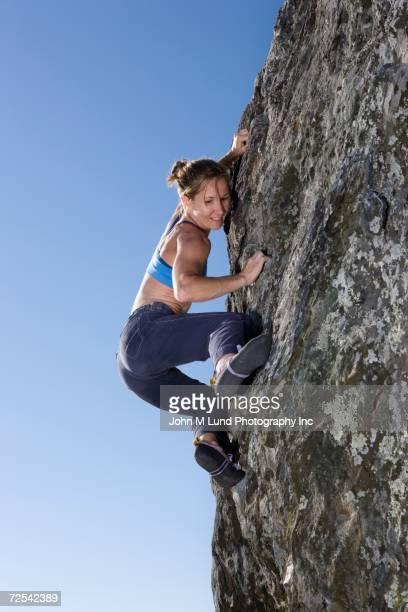 Low angle view of woman rock climbing