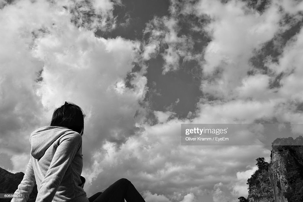 Low Angle View Of Woman Sitting Against Sky : Stock Photo