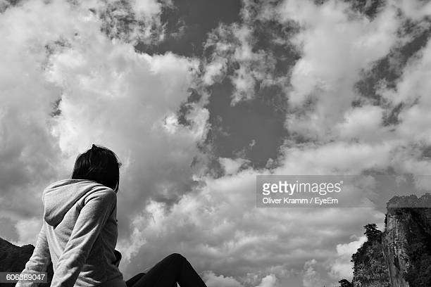 Low Angle View Of Woman Sitting Against Sky