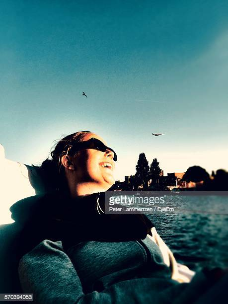 Low Angle View Of Woman Sitting In Nautical Vessel At River