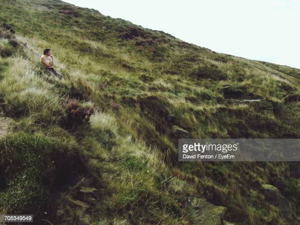 Low Angle View Of Woman Sitting On Grassy Mountain Against Clear Sky