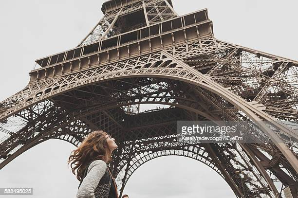 Low Angle View Of Woman Standing In Front Of Eiffel Tower