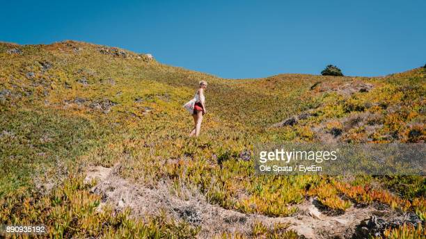 Low Angle View Of Woman Standing On Mountain Against Clear Sky