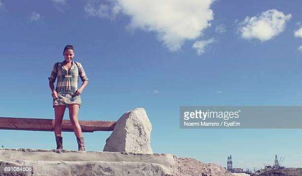 Low Angle View Of Woman Standing On Steps Against Blue Sky