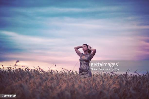 Low Angle View Of Woman Standing On Wheat Field Against Cloudy Sky During Sunset