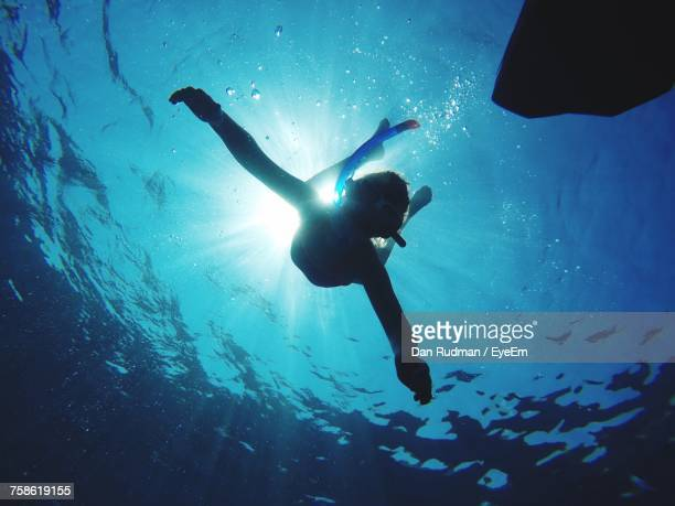 Low Angle View Of Woman Swimming Undersea During Sunny Day