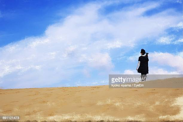 Low Angle View Of Woman Walking At Tottori Sand Dunes Against Sky