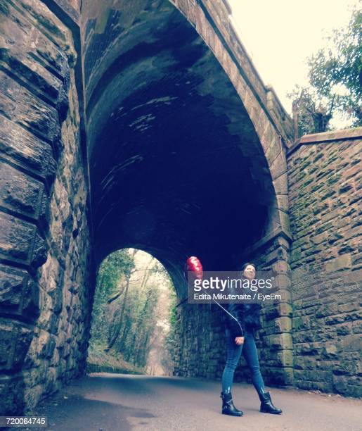 Low Angle View Of Woman With Balloon Standing On Archway