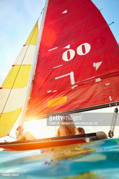 Low angle view of women riding in sailboat on ocean