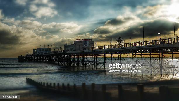 Low Angle View Of Worthing Pier Over Sea Against Cloudy Sky During Sunset