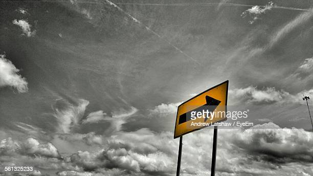 Low Angle View Of Yellow Direction Sign Board Against Cloudy Sky