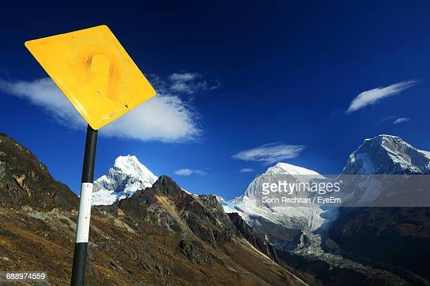 Low Angle View Of Yellow Signpost By Mountain Peaks Against Blue Sky