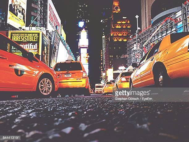 Low Angle View Of Yellow Taxi Amidst Illuminated Buildings At Times Square
