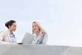 Low angle view of young businesswomen with laptop discussing while standing on terrace against sky
