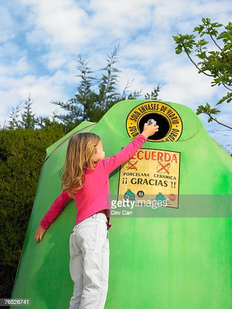 Low angle view of young girl putting glass bottle in recycling bin, Alicante, Spain,
