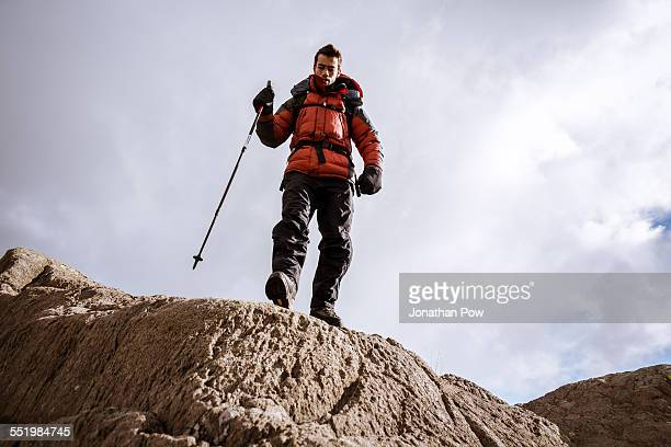 Low angle view of young male hiker on rocks, The Lake District, Cumbria, UK