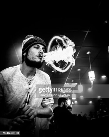 Low Angle View Of Young Man Making Smoke Ring In Restaurant : Stock Photo